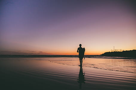silhouette photo of man standing seashore during golden hour
