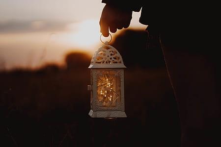 person holding white lamp lantern