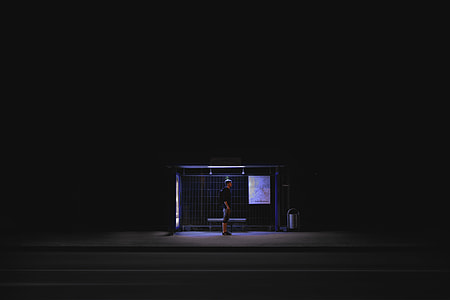 man in black shirt standing on waiting shed