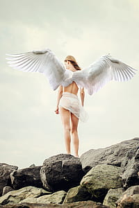 angel standing on rock under cloudy sky