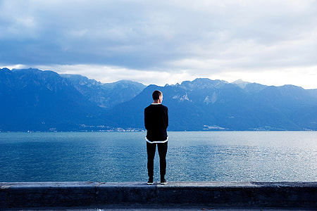man in black sweater facing the alps across the calm sea during daytime