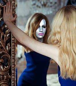 woman wearing blue dress leaning on mirror