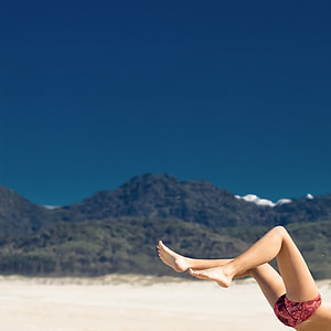 person with pink and black underwear flipping on white sand under blue sky