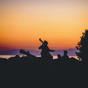 silhouette of woman playing cello