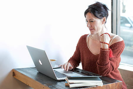woman sitting on chair using MacBook