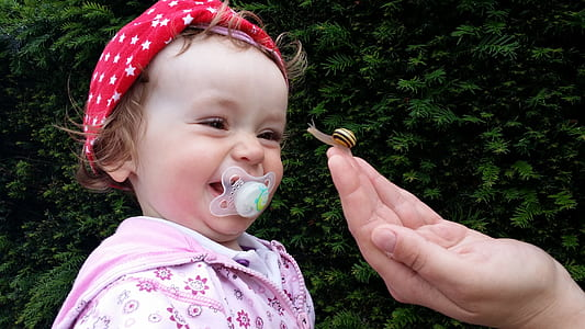 girl's biting white pacifier