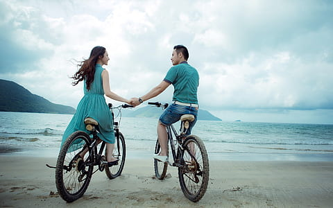 man and woman riding bicycle on seashore