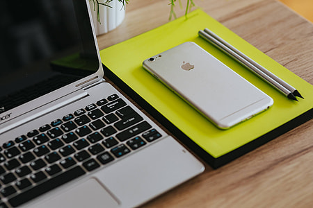 Silver Acer laptop, a white Apple iPhone and a notepad on a wooden desk