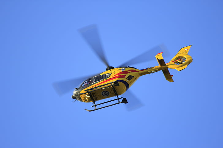 low angle photographed of flying yellow helicopter