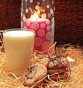 chocolate chip cookies beside glass of milk and red pillar candle