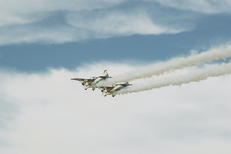 two white dog fighter planes throwing smoke on air under white cloudy skies