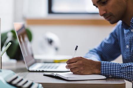 man in plaid dress shirt writing on the desk