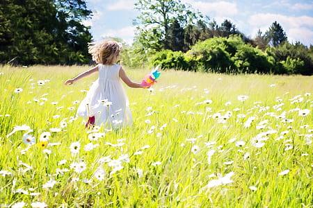 girl running in white flower field