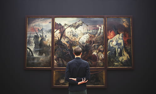 man in black dress shirt looking at paintings