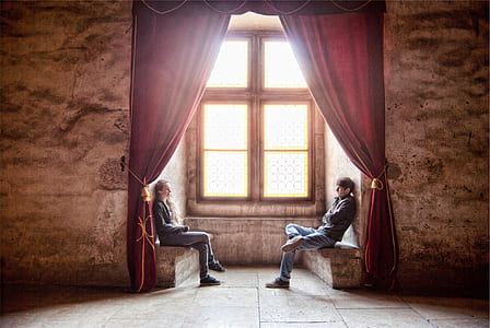 photo of man and woman sitting on terrace beside a window