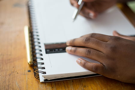 person holding ruler and drafting pen