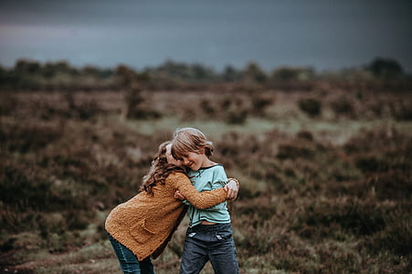 girl and child playing outside photography during daytime