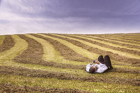 man in white dress shirt and brown dress pants outfit lying at green grass field