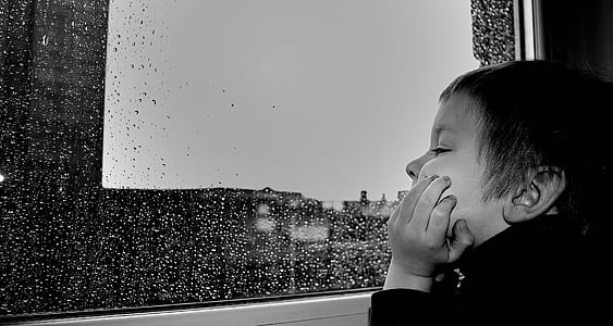 grayscale photography of boy watching the rain on window
