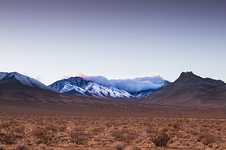 snowy mountains under cloudy sky