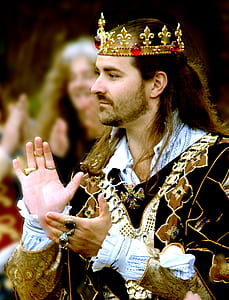 man in black and gold suit and gold crown