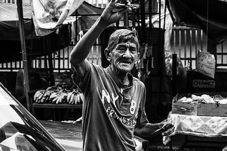 grayscale photo of man wearing polo shirt in a market
