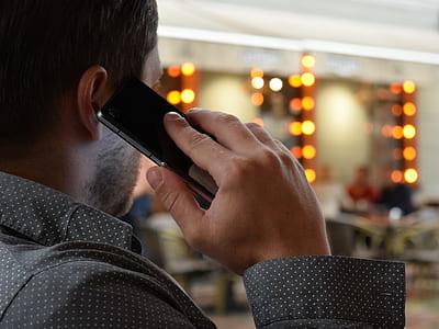 man holding smartphone wearing dress shirt