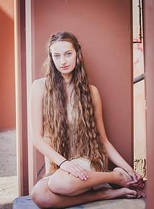 woman wearing dress sitting on floor near the wall