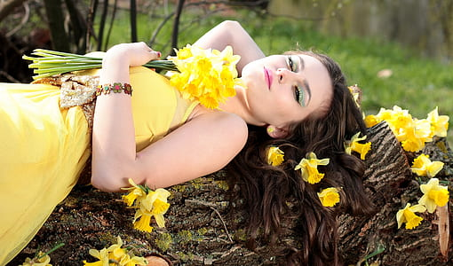 woman in yellow dress lying on top of brown tree log
