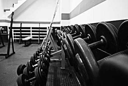 assorted dumbbells in grayscale photography
