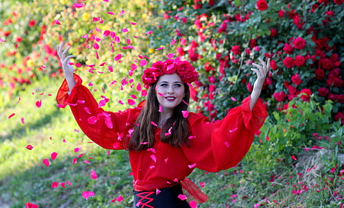 woman wearing red rose crown showering petals