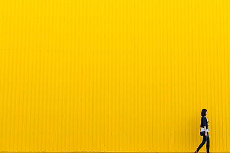 woman in black pants and cardigan walking beside yellow wall