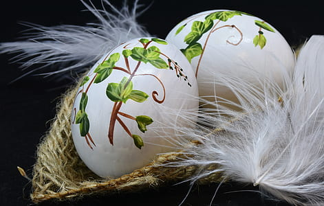 two white-and-green easter eggs on brown wicker basket