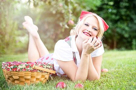 smiling woman wearing white collared shirt lying on ground