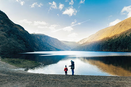 two person standing near water