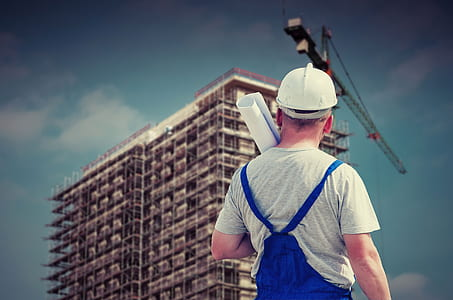 man in white hard hat, gray crew-neck t-shirt and blue jumpsuit holding paper watching building