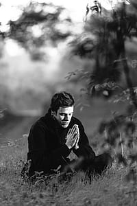 grayscale photograph of man sitting on grass