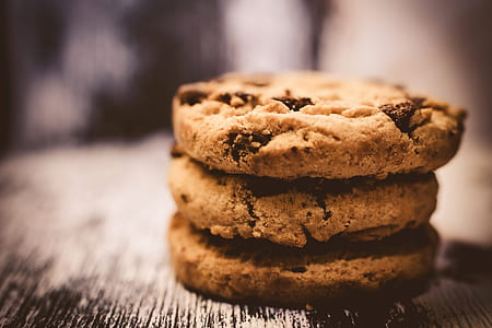 selective photo of three brown cookies on gray board