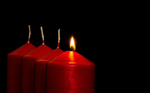 one lighted of four pillar candles