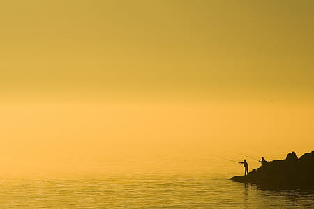 silhouette of person holding fishing rod