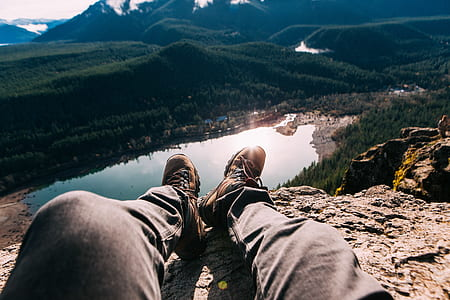 person sitting on rock cliff