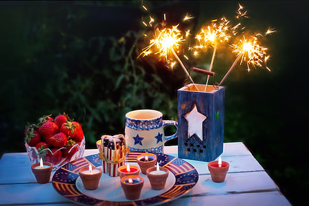 sparkler on container beside tealights on table