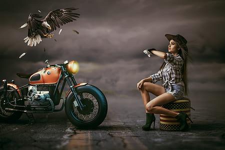 woman sitting near orange motorcycle and eagle