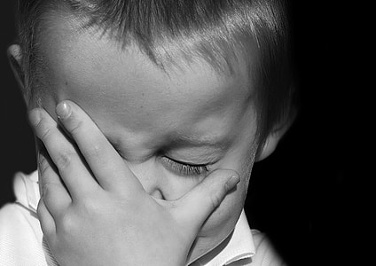 grayscale photography of boy holding his face