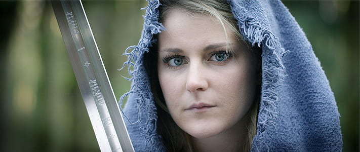 woman wearing blue hood holding gray sword