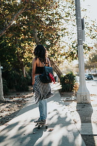 woman riding on skateboard beside the lamp post