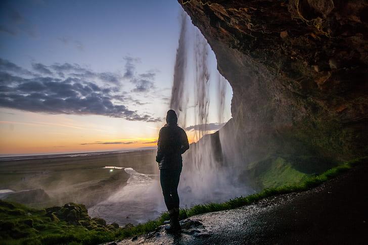 person standing under waterfalls