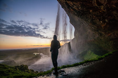 person standing under waterfalls