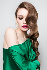 woman wearing gold earrings and green blouse