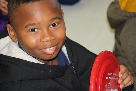 boy wearing black hoodie holding red plastic toy